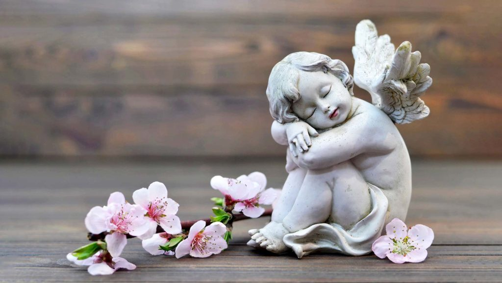 ceramic angel surrounded by flowers carlyle funerals