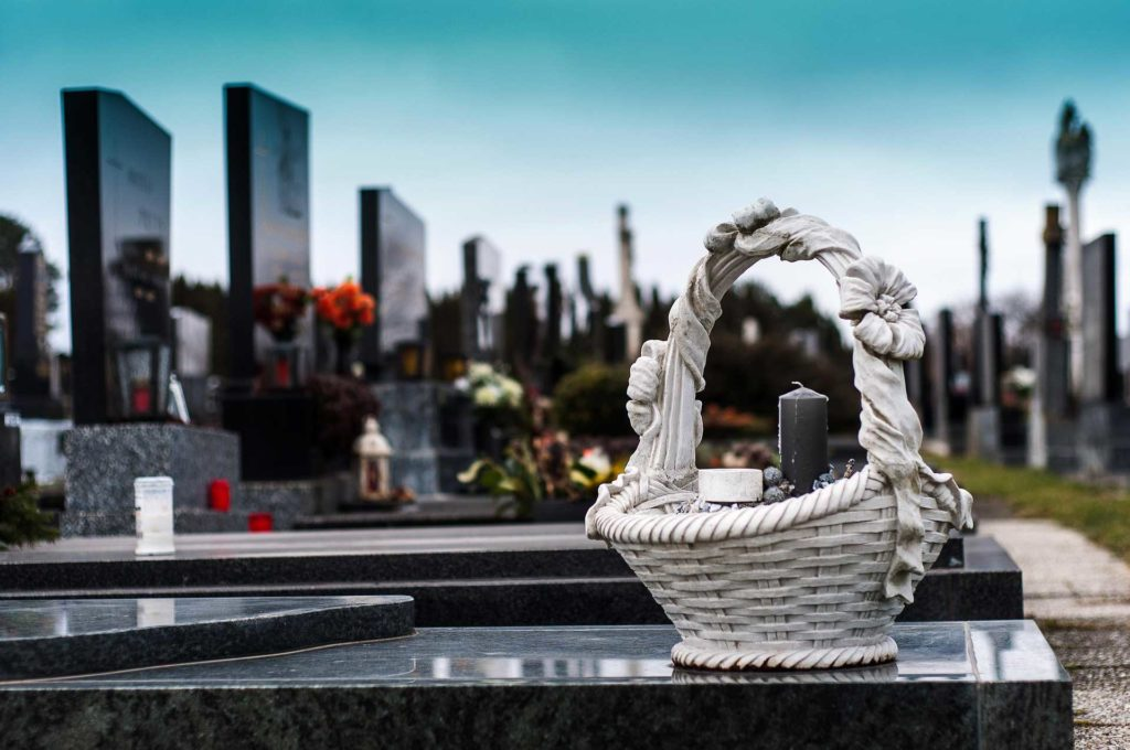 Carlyle Family Funerals hero image of marble headstones with wicker basket and candles